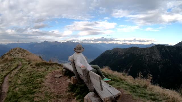 vidéos et rushes de le randonneur féminin détend sur la chaise de notation, à la fin de la randonnée - quinquagénaire