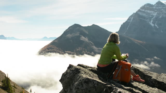 female hiker relaxes on mountain crest above fog, forest - solo una donna matura video stock e b–roll