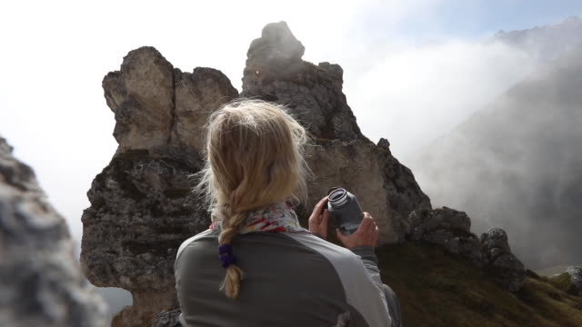 vídeos de stock e filmes b-roll de female hiker relaxes on mountain slope, drinks water - beber