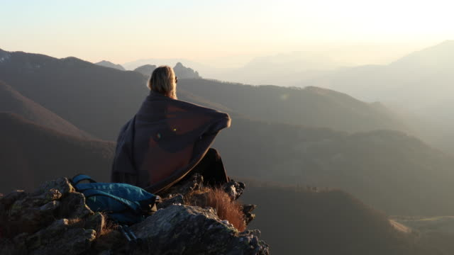 Female hiker relaxes on mountain summit, in blanket