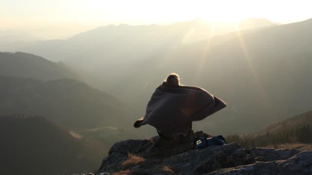 female hiker relaxes on mountain summit, in blanket - bedecken stock-videos und b-roll-filmmaterial