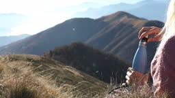 Female hiker relaxes on mountain summit, with water bottle