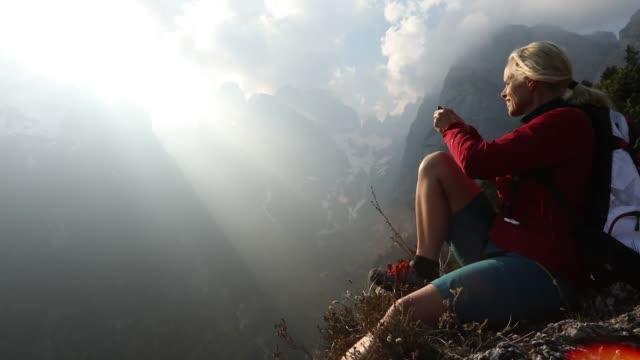女性ハイカーが日の出崖端で寛ぎます - トレンティーノ点の映像素材/bロール