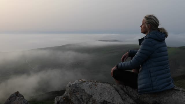 female hiker relaxes on rock bluff, above hills - republic of cyprus stock videos and b-roll footage