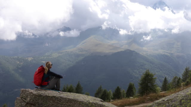 Female hiker relaxes on rock slab, looks out to mountain scene