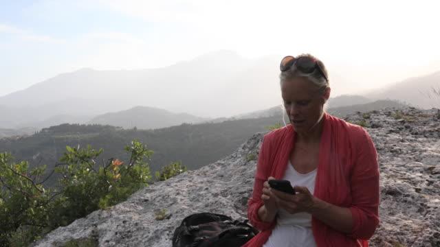 vídeos y material grabado en eventos de stock de female hiker relaxes on rocky perch above valley - mochila bolsa