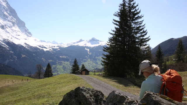 Female hiker relaxes, then walks along track through mountain meadow
