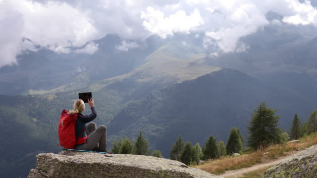 female hiker relaxes while using digital tablet, looks out to mountain scene - convenience stock videos & royalty-free footage