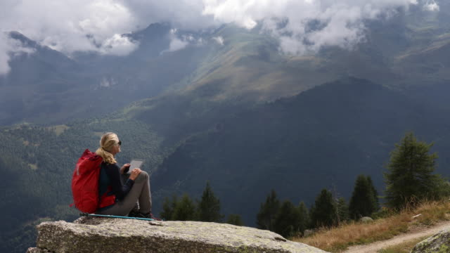 Female hiker relaxes while using digital tablet, looks out to mountain scene