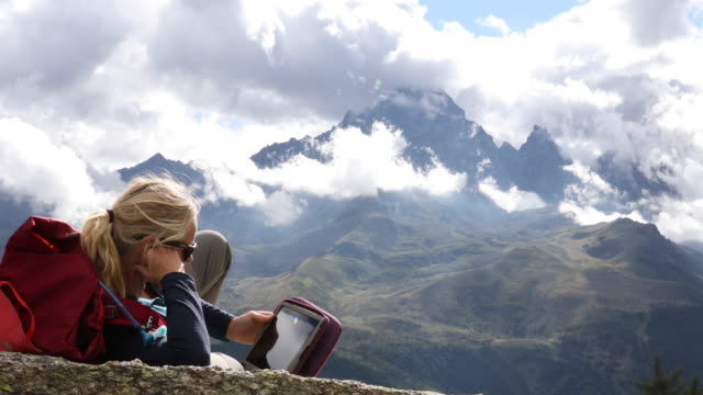 female hiker relaxes while using digital tablet, looks out to mountain scene - rucksack stock videos & royalty-free footage