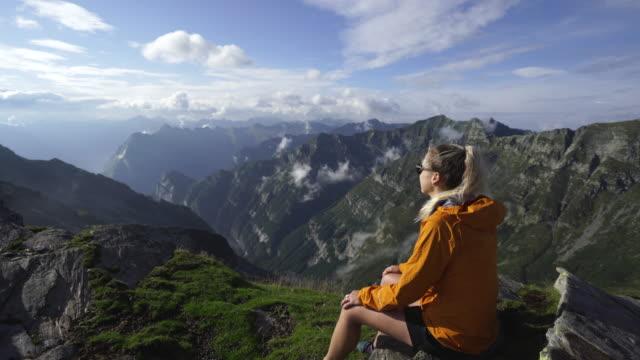 vídeos de stock, filmes e b-roll de o caminhante fêmea senta-se na parte superior da montanha para apreciar a vista do por do sol - laranja descrição de cor