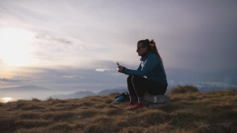 stockvideo's en b-roll-footage met de vrouwelijke wandelaar zit op bergbovenkant gebruikend smartphone om te sms'en en te roepen - solitair