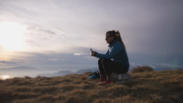 female hiker sits on mountain top using smartphone to text and call - serene people stock videos & royalty-free footage