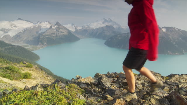 ws ha female hiker sitting down on edge of cliff overlooking lake surrounded by snow capped mountains, garibaldi provincial park, squamish, british columbia, canada - cliff stock videos & royalty-free footage