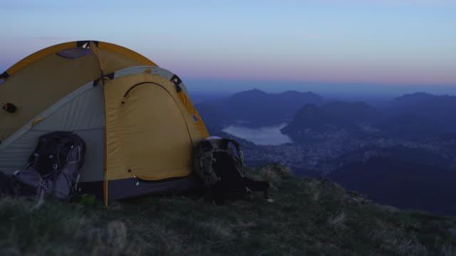 vídeos y material grabado en eventos de stock de el excursionista femenino sentado en la entrada de su carpa en la cima de una montaña - idílico
