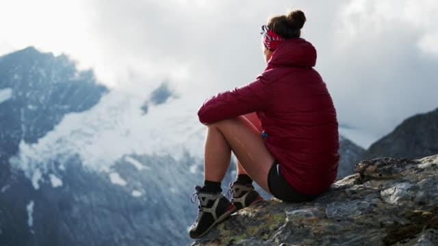 wanderin sitzt auf einem felsen in den bergen mit schnee - erforschung stock-videos und b-roll-filmmaterial
