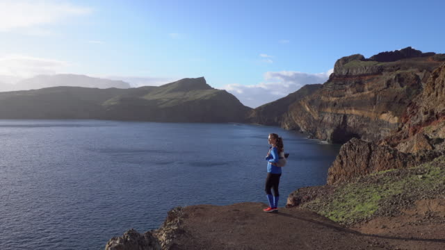 female hiker standing on rocky looking at sunrise in madeira - madeira stock videos and b-roll footage