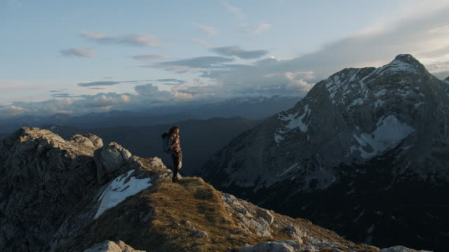 female hiker standing on the edge of a hill looking into the distance - stillstehen stock-videos und b-roll-filmmaterial