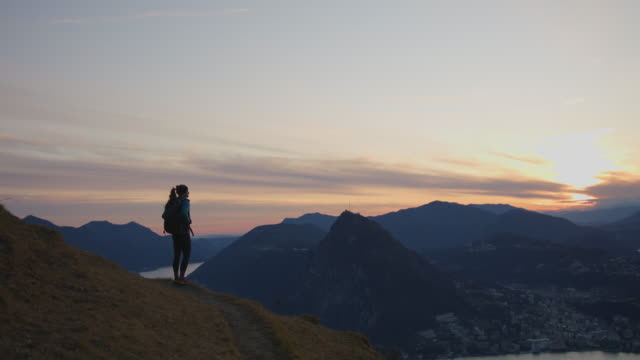 vídeos de stock e filmes b-roll de female hiker stands on mountain top overlooking view and sunset - switzerland