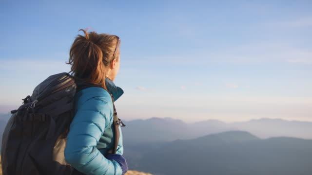 wanderin steht auf dem berggipfel, atmet tief durch, genießt die aussicht - mountain range stock-videos und b-roll-filmmaterial