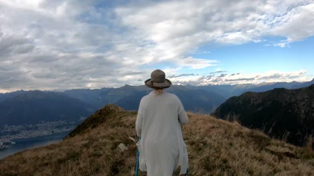 vidéos et rushes de le randonneur femelle marche à travers le crête alpin - quinquagénaire
