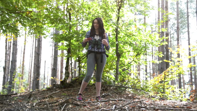 Female hiker takes a photo in the forest with a phone