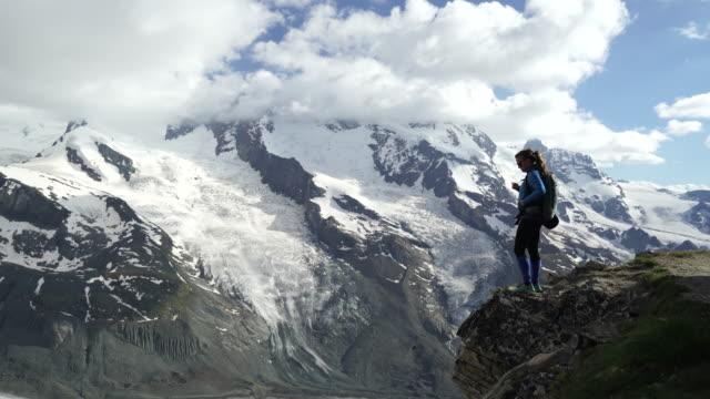 Kvinnliga vandrare tar telefonen foto från toppen av berget med utsikt över Gorner Glacier