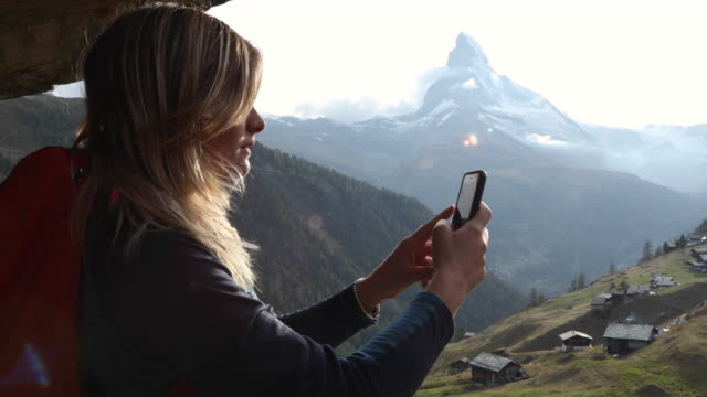 female hiker takes smart phone pic of matterhorn - photographing stock videos & royalty-free footage