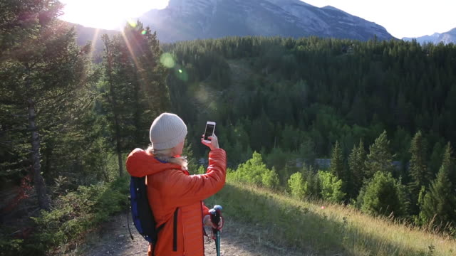 Female hiker takes smart phone pic of mountains and forest