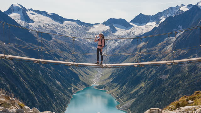 female hiker taking a refreshing break, standing on a hanging bridge over mountain stream, enjoying breathtaking view of mountain valley lake and surrounding mountains - austria stock videos & royalty-free footage