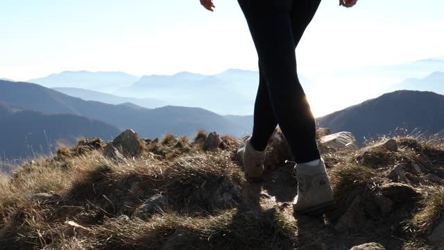 wanderin durchquert grasbewachsenen berggipfel - menschliche gliedmaßen stock-videos und b-roll-filmmaterial