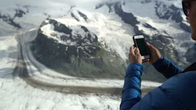female hiker uses phone on top of mountain - cappotto invernale video stock e b–roll