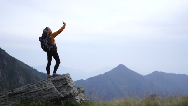 female hiker using smartphone in nature on top of mountain in nature - photographing stock videos & royalty-free footage