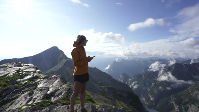 female hiker using smartphone on mountain top - jacket stock videos & royalty-free footage