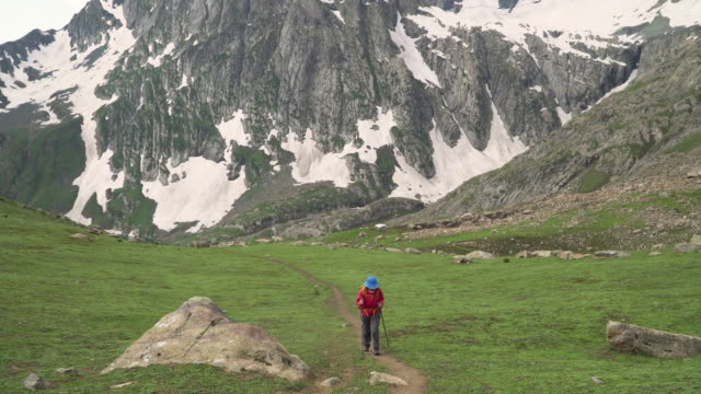 female hiker walk away near the rocky mountain peak - tilt up stock videos & royalty-free footage