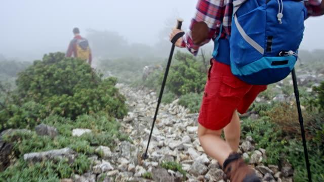 Female hiker walking down the mountain behind her female friend in heavy fog