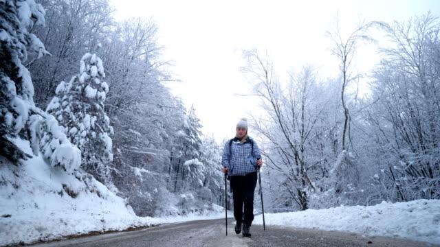 Vrouwelijke wandelaar lopen op een weg door het besneeuwde forest