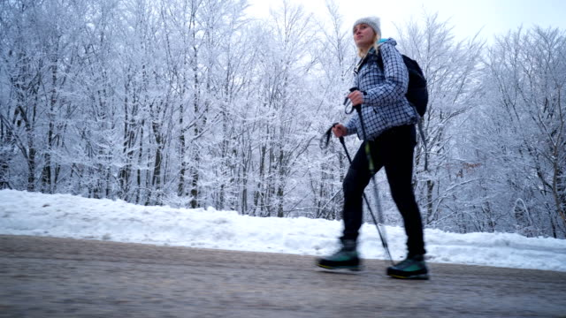 female hiker walking on a road by the snowy forest - hiking pole stock videos and b-roll footage