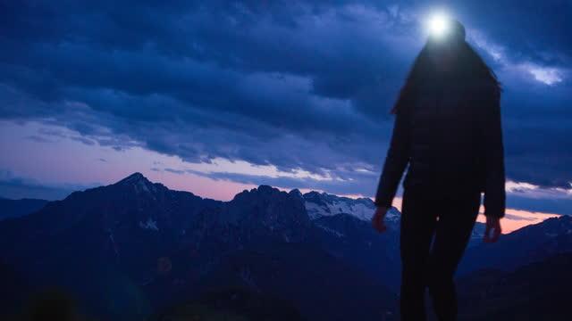 vidéos et rushes de randonneur femelle marchant sur le sentier rocheux de montagne au crépuscule avec la lampe de tête sur - lampe frontale