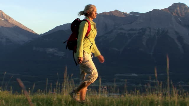 WS, PAN, female hiker walking towards sun across mountain meadow, Canmore, Alberta, Canada