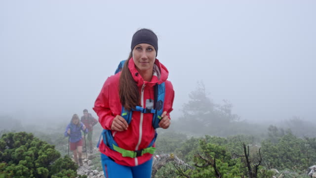 Female hiker walking up the foggy mountain with her friends