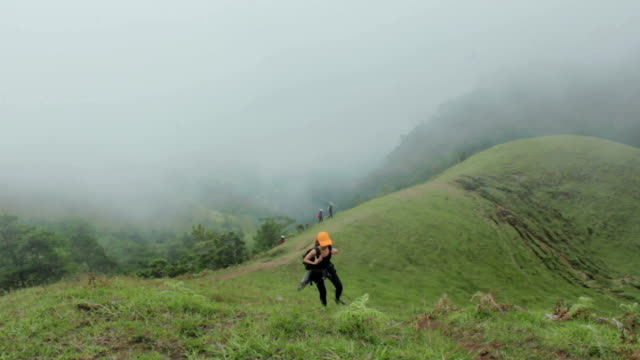 female hiker walking uphill - grass stock videos & royalty-free footage