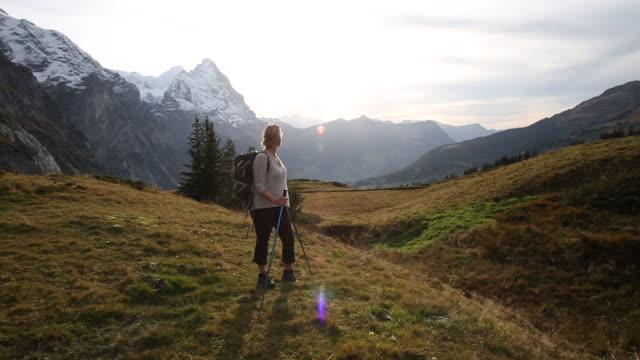 female hiker walks across mountain meadow - eskapismus stock-videos und b-roll-filmmaterial