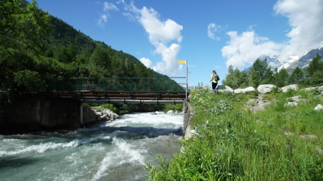 Female hiker walks along alpine river, stops to check direction