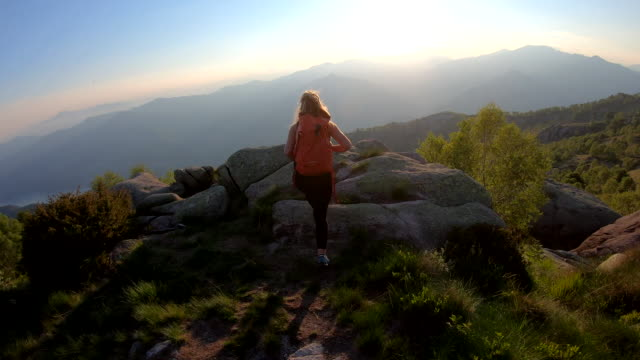 vídeos de stock e filmes b-roll de female hiker walks along mountain ridgetop at sunrise - cabelo comprido