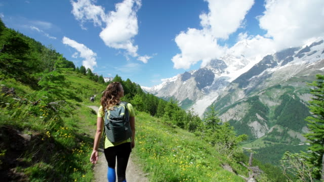 Female hiker walks along mountain trail below snowcapped mountains
