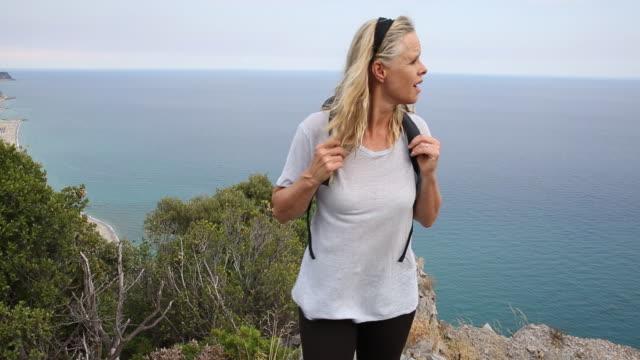 vídeos de stock e filmes b-roll de female hiker walks along ridge above sea - só uma mulher madura