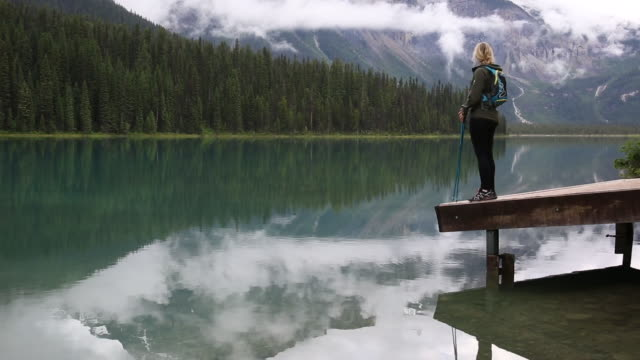 female hiker walks onto mountain dock after rainstorm - jetty stock videos & royalty-free footage