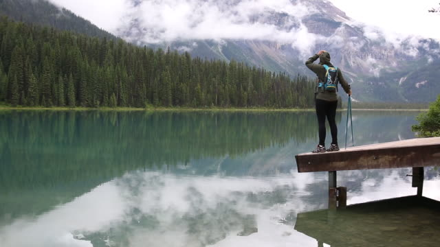 Female hiker walks onto mountain dock after rainstorm