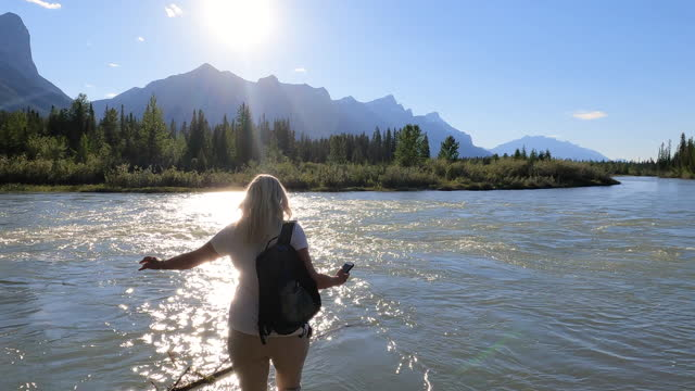 female hiker walks out to river's edge, takes pic - clear sky stock videos & royalty-free footage